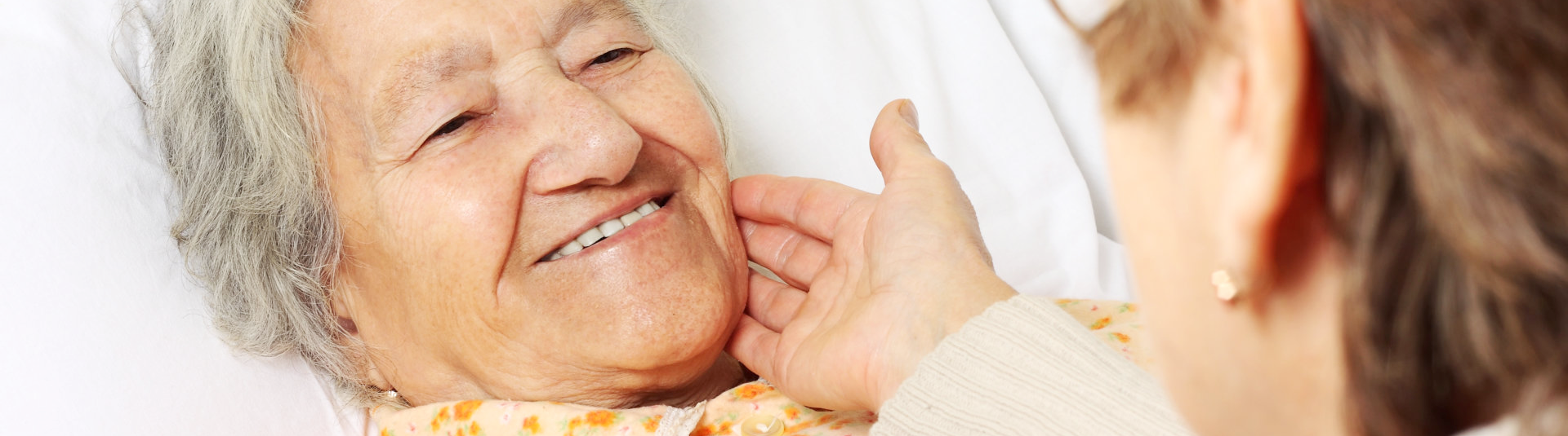 Old woman in the bed is smiling on her caregiver