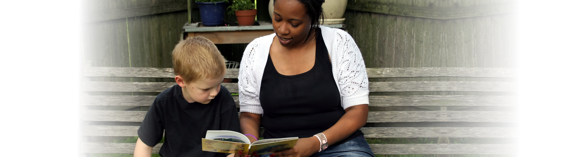 Woman is teaching the boy to read
